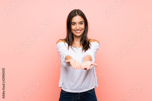 Obraz Young woman over isolated pink background holding copyspace imaginary on the palm to insert an ad - fototapety do salonu