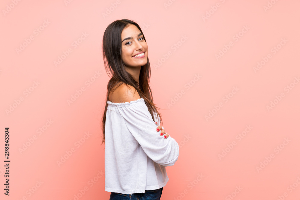 Fototapeta Young woman over isolated pink background with arms crossed and looking forward