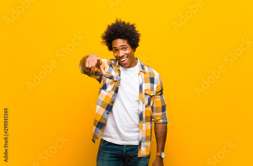 Fotomural  young black man pointing at camera with a satisfied, confident, friendly smile,