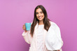 canvas print picture - Young woman in pajamas and dressing gown over isolated purple background holding a cup of coffee