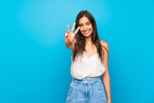 Young Woman Over Isolated Blue Background Happy And Counting Three With Fingers