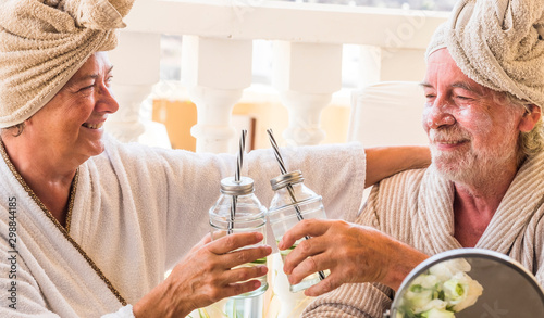couple of two seniors in a resort or hotel drinking a cocktail and clincking - pensioners relaxed with a beauty treatment