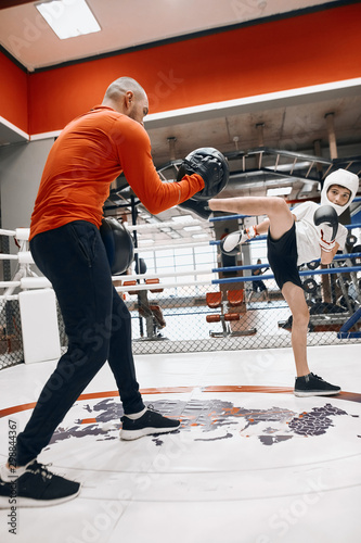 Photo Young hardworking kickbox fighter hitting mitts with his coach, boy with raised leg striking his teacher