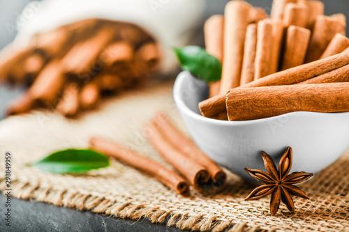 Fototapeta Fresh cinnamon sticks with anise star in white porcelain bowl. Cinnamons bunch in background. obraz