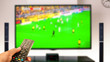 canvas print picture - watching soccer at home tv with remote control on hand