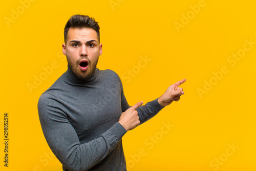 young hispanic man feeling shocked and surprised, pointing to copy space on the Canvas Print