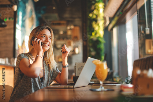 Beautiful young woman talking on the phone in cafe with a laptop on the table in front of her and looking out the window - 298852713