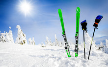Skis In Snow With Gloves Copy Space. Green Skis Standing In Heavy Snowy Winter And Forest Frozen Trees Or Mountains In Background. Winters Holiday Skiing Concept.