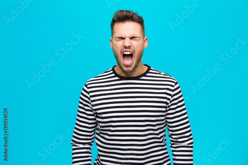Fotografía young hispanic man shouting aggressively, looking very angry, frustrated, outrag