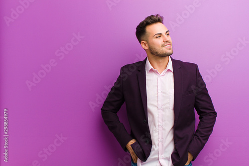 Fotomural  young hispanic man looking happy, cheerful and confident, smiling proudly and lo