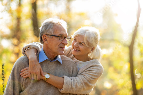 Elderly couple embracing in autumn park  - 298855116