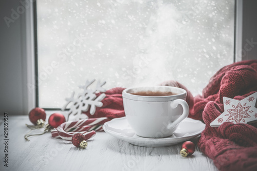 Obraz na plátně  Winter cozy hot chocolate in front of window, snow, sweater