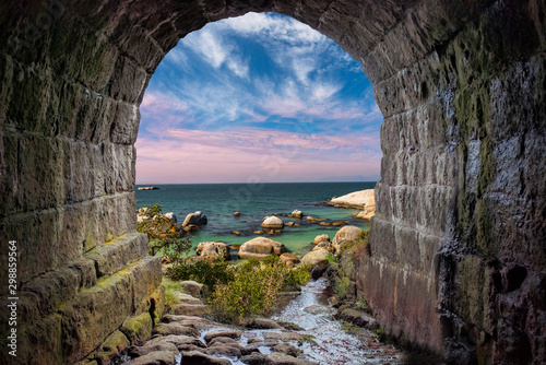 Fotomural  Boulders beach through a stone tunnel Cape Town