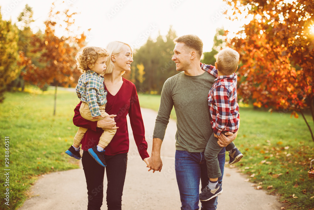 Fototapety, obrazy: Beautiful young family walking in park and having fun with kids