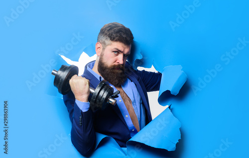 Photo Businessman with dumbbell looking through paper hole