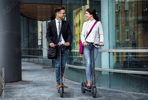 Two smiling business people driving electric scooter in front of modern business building going on work. - 298864115