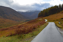 Single Track Road Through Glen Etive, Scottish Highlands With Snow Capped Mountains In Background