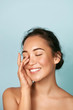 canvas print picture - Beauty face. Smiling asian woman touching healthy skin portrait. Beautiful happy girl model with fresh glowing hydrated facial skin and natural makeup on blue background at studio. Skin care concept