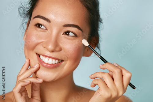 Beauty. Woman applying makeup on eyes with cosmetic brush closeup. Portrait of happy smiling asian girl model with beautiful face applying facial make up at studio