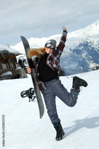 Poster Glisse hiver Woman snowboarder posing at the ski slope in Courchevel France.