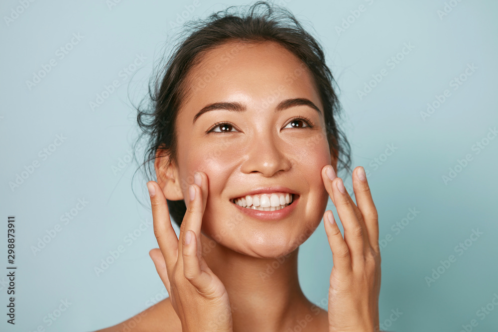 Fototapety, obrazy: Beauty face. Smiling asian woman touching healthy skin portrait. Beautiful happy girl model with fresh glowing hydrated facial skin and natural makeup on blue background at studio. Skin care concept