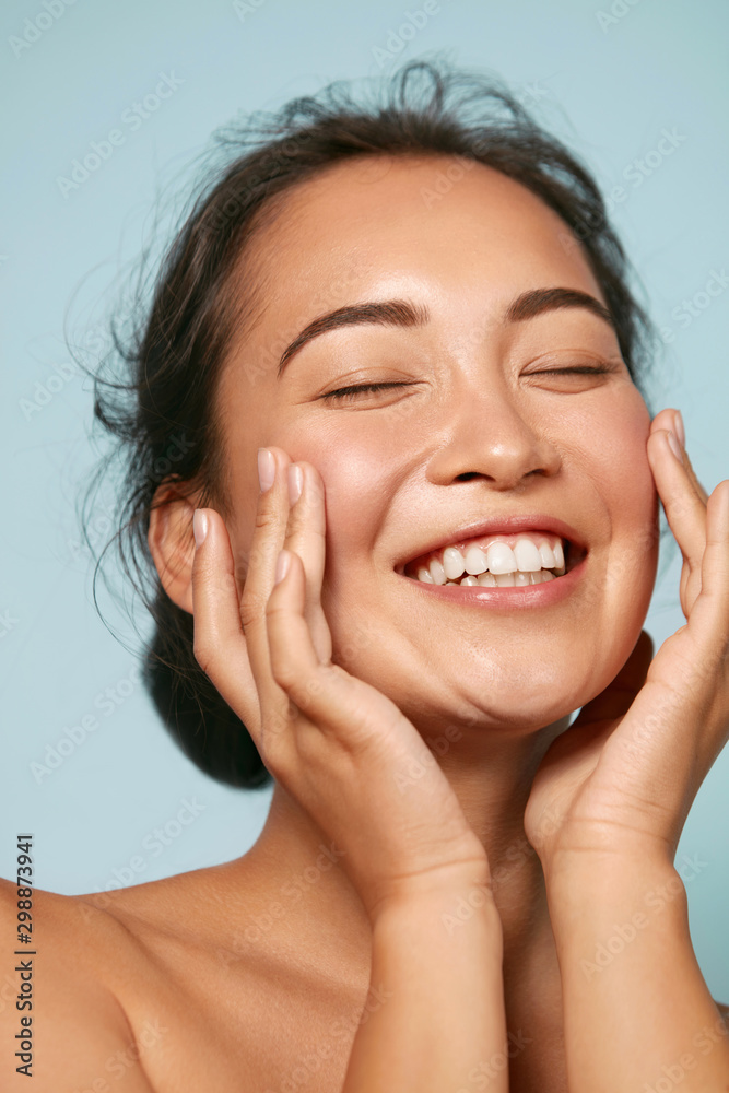 Fototapeta Skin care. Woman with beauty face touching healthy facial skin portrait. Beautiful smiling asian girl model with natural makeup touching glowing hydrated skin on blue background closeup