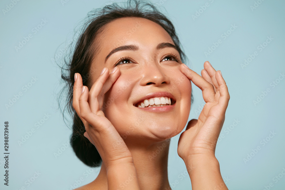 Fototapety, obrazy: Skin care. Woman with beauty face touching healthy facial skin portrait. Beautiful smiling asian girl model with natural makeup touching glowing hydrated skin on blue background closeup