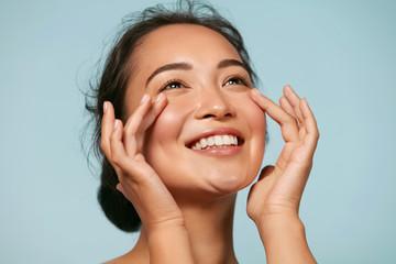 Briga o koži. Žena s ljepotom lica dodiruje zdrav portret kože lica. Prekrasan nasmijani azijski model djevojke s prirodnom šminkom dodirujući užarenu hidratiziranu kožu na plavoj pozadini izbliza