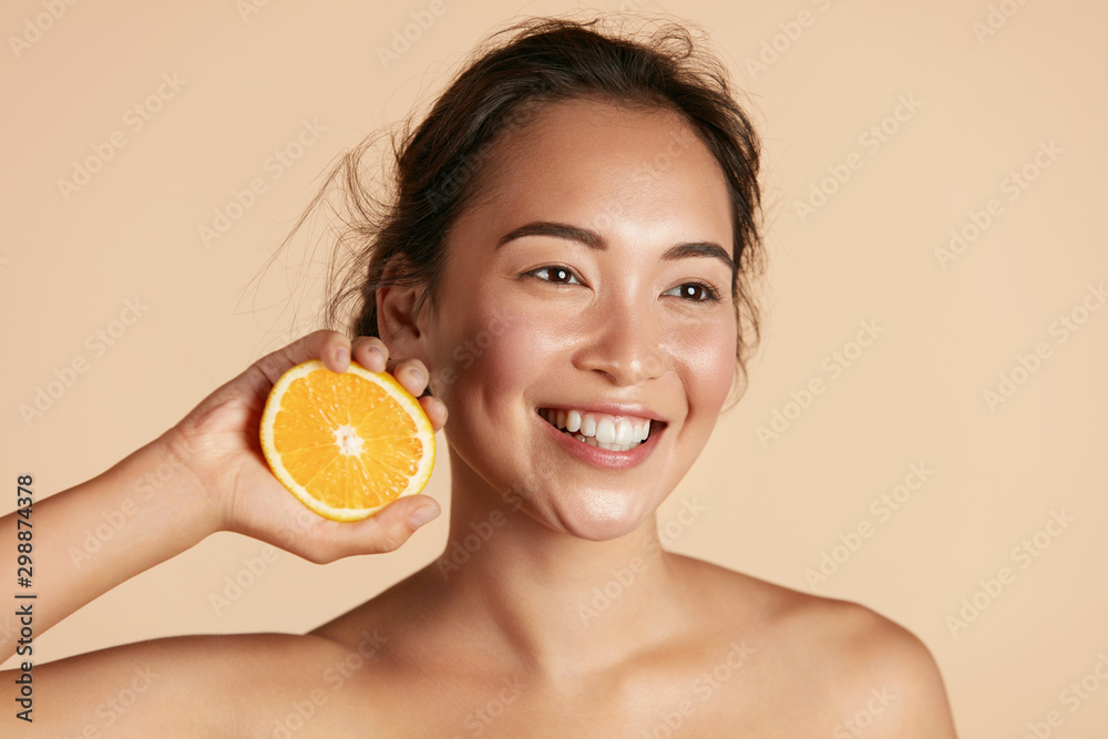 Fototapeta Beauty. Smiling woman with radiant face skin and orange portrait. Beautiful smiling asian girl model with natural makeup, healthy smile and glowing hydrated facial skin. Vitamin C cosmetics concept