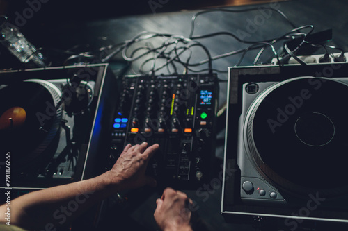 Dj hands on equipment deck and mixer with vinyl record at party. - 298876555