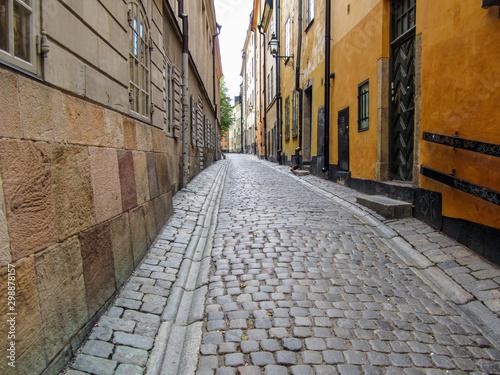 Fototapeten Schmale Gasse Narrow alley with cobblestone