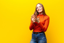 Young Pretty Woman Feeling Happy And Successful, Smiling And Clapping Hands, Saying Congratulations With An Applause Against Orange Background