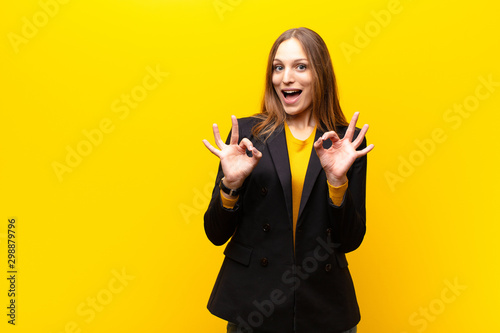 Photographie  young pretty businesswoman feeling shocked, amazed and surprised, showing approv