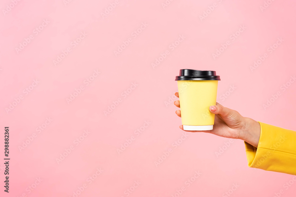 Fototapety, obrazy: cropped view of woman holding yellow disposable cup of coffee, isolated on pink