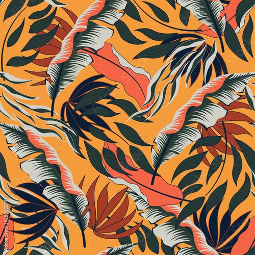 Tropikalny bezszwowy lato wzór z jaskrawymi czerwonymi i zielonymi liśćmi i roślinami na żółtym tle. Kolorowy wzór hawajski lato z tropikalnych roślin. Piękny nadruk z ręcznie rysowanym rysunkiem.