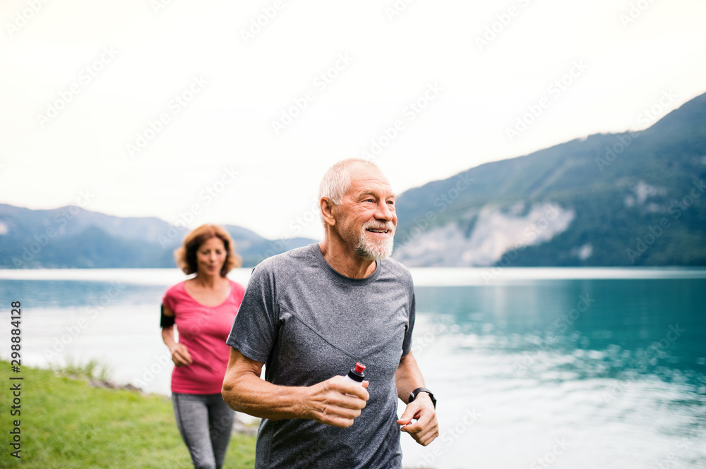 Fototapety, obrazy: Senior pensioner couple with smartphone running by lake in nature.