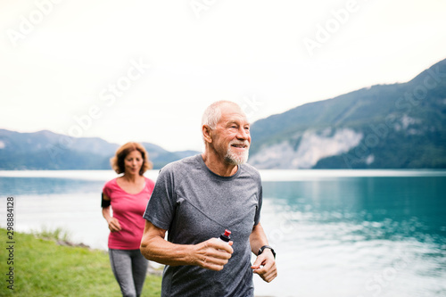 Leinwand Poster  Senior pensioner couple with smartphone running by lake in nature