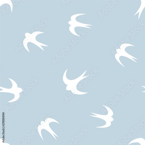 Fotografía  Seamless pattern with white silhouettes of swallows on blue background