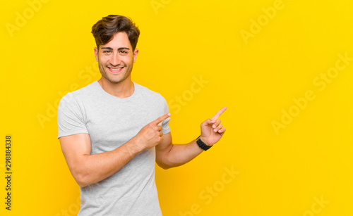 Cuadros en Lienzo smiling happily and pointing to side and upwards with both hands showing object