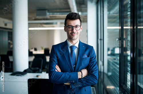 Fototapeta A portrait of young businessman standing in an office, looking at camera. obraz