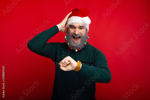 Photo of man with white decorated beard looking confused at watch