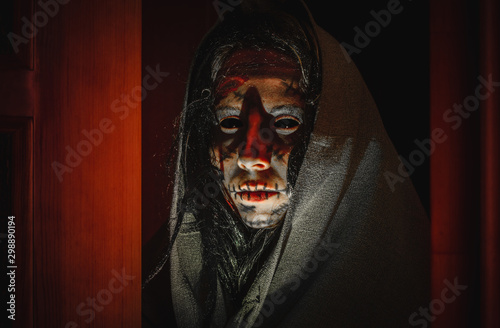Leinwand Poster Creepy halloween witch with black eyes, scars on her face in a hood stands near