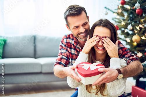 Portrait of man surprising girlfriend with present Billede på lærred