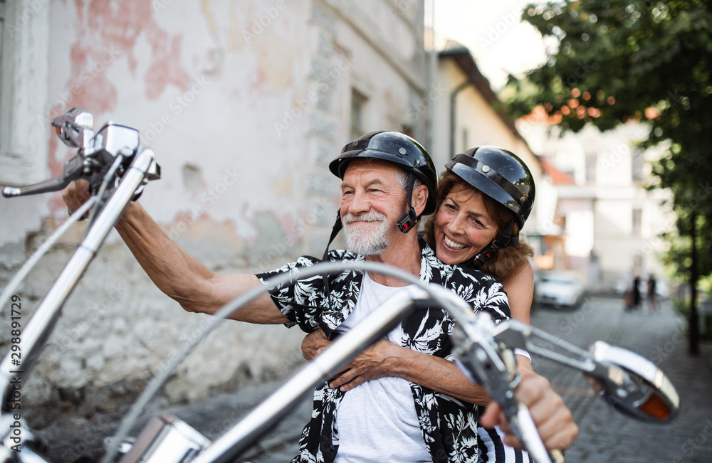 Fototapeta A cheerful senior couple travellers with motorbike in town.