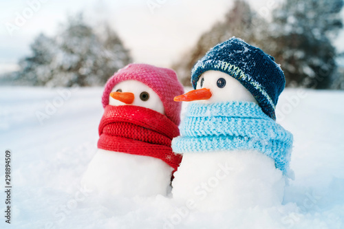 Obraz Two small snowmen the girl and the boy on snow, copy space. Greeting card for lovers, Christmas card - fototapety do salonu