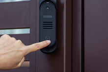 A Woman Presses The Bell Button On The Front Door