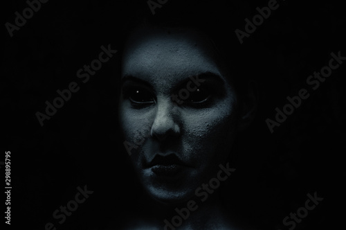 Fototapeta Scary and frightening  demonic woman face with black eyes in the dark