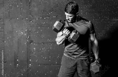 Young strong muscular sweaty man biceps muscle workout training with heavy dumbbell weight in the gym dark image with shadows real people black and white