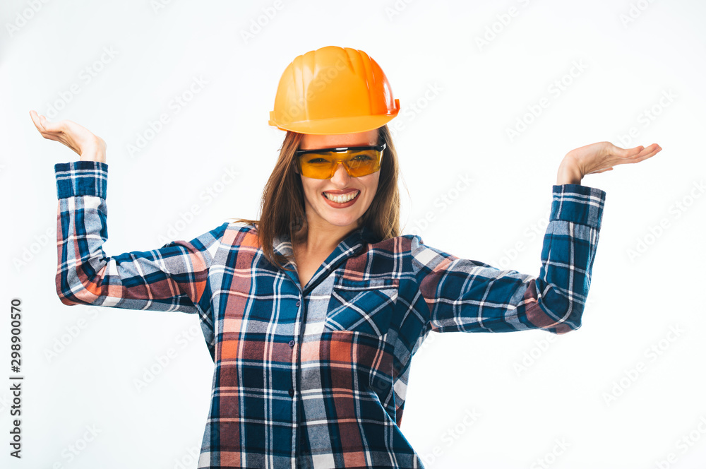 Fototapety, obrazy: Happy young woman is wearing orange safety helmet, yellow glasses and checkered shirt holding hands wide. Isoalted background. Closeup.