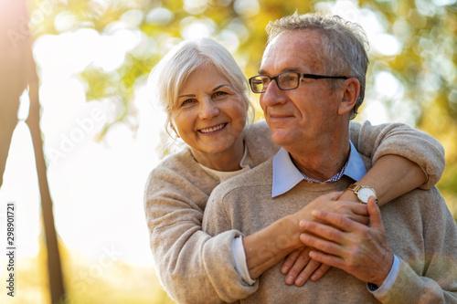 Stampa su Tela  Elderly couple embracing in autumn park